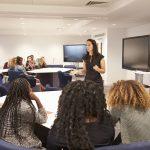Female,Teacher,Addressing,University,Students,In,A,Classroom